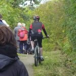 Photograph of cyclist riding past walkers