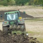 Photograph of green ractor ploughing field