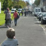 Photograph of people walking near village green towards Villahge Hall