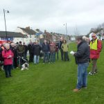 Photograph of people listening to opening speech on village green