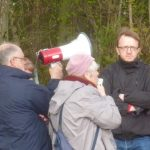 Photograph of people listening to talk with an man next to a loudhailer