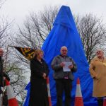 Photograph of sculpture waiting to be unveiled in blue cover