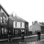 Photograph of men on biles in front street