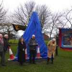 Photograph of banner sflying next to scultpture during the unveiling speeches