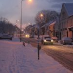 Photograph of snowy front street at dusk with traffic