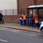 Photograph of volunteer litter pickers near bus shelter