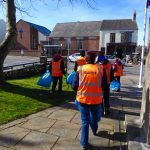 Photograph of volunteer litter pickers picking up waste on way back to village hall