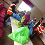 Photograph of volunteers in village hall with litter picking equiptment and bags