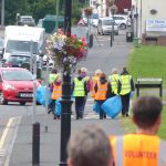 Photograph of volunteer litter pickers in front street at distance
