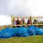 Group photograph of volunteers with bags of rubbish taken at distance through fence