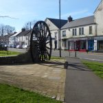 Photograph of pit wheel with shadow and front steet in background