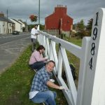 Volunteers at work painting final coat onto gate