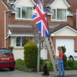 Two people erecting a flag while dog looks on