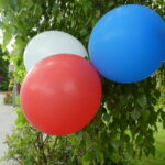 blue red and white balloons with tree in background