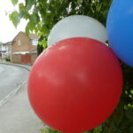 a set of three balloons blue, red and white baloons