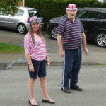 residents with union flag hats on their daily walk